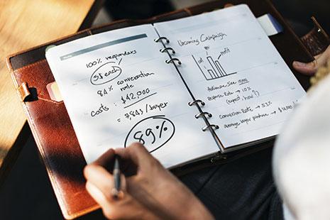 Mano con bolígrafo sobre una libreta abierta con letras, números y gráficos