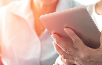 Manos de persona mayor sujetando una tablet
