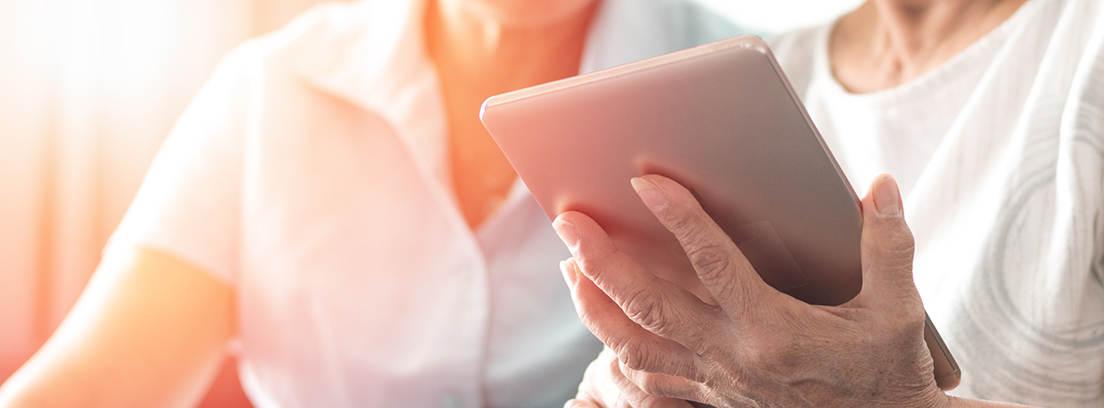 Dos personas mayores mirando unas tablets