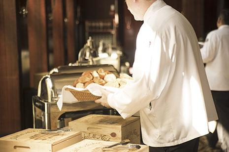 Hombre con chaqueta blanca sujetando una bandeja de panes
