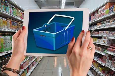 Manos sujetando una Tablet con una cesta de la compra en la pantalla y estanterías de supermercado