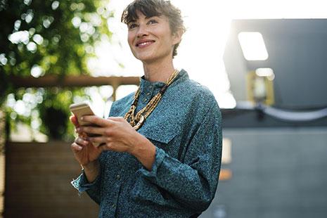 Mujer con Smartphone entre las manos mira hacia el infinito con sonrisa