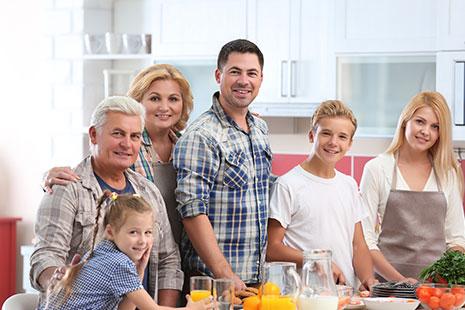 Dos hombres, dos niños y dos mujeres delante de una mesa con vasos, jarras y alimentos