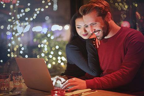 Hombre sonriente con manos sobre teclado de portátil y mujer apoyada en su hombro