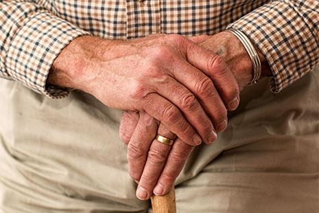 Manos de persona mayor apoyadas en un bastón