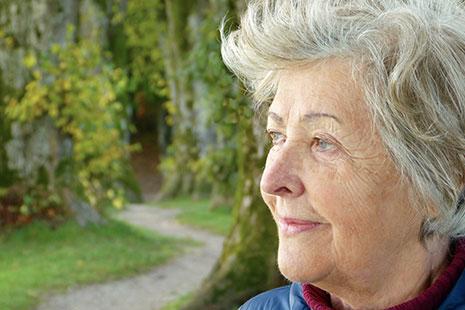 Primer plano de mujer con pelo blanco con un bosque de fondo