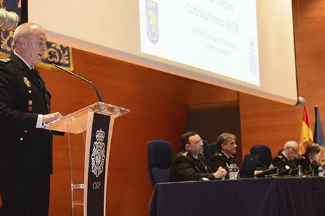 Hombre con uniforme de policía delante de un atril junto mesa con otros hombres