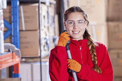 Mujer con gafas, chaqueta roja y guates naranjas sujeta un bastón metálico