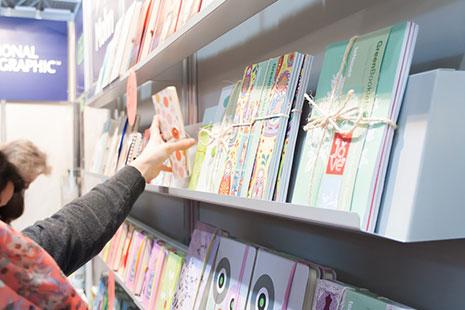 Expositor de tienda con libros y mano cogiendo uno de ellos