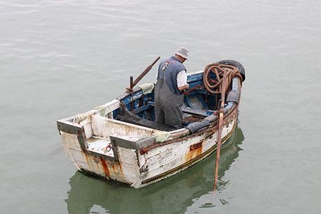 Pescador montando en una pequeña barca
