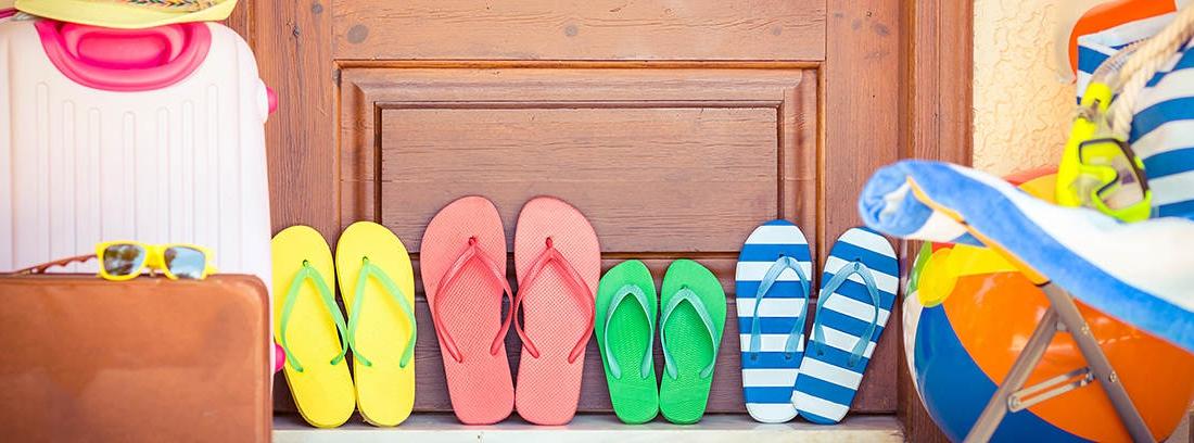 Maletas, sandalias, gorro, pelota y gafas de sol frente a la puerta de una casa