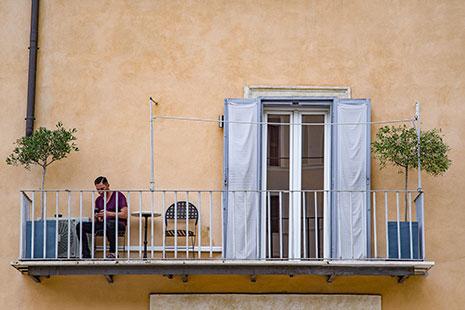 Hombre sentado en un balcón con árboles y puerta abierta
