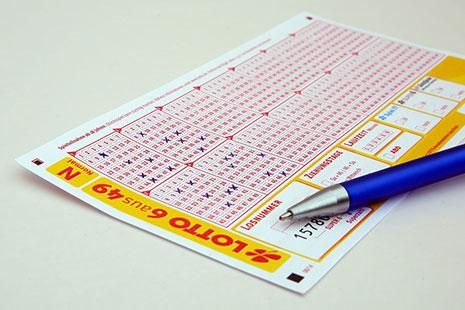Boleto de lotería con números rojos y un bolígrafo sobre él