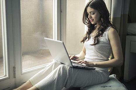 Mujer sentada junto a un cristal con un ordenador portátil sobre sus rodillas