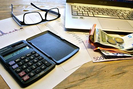 Calculadora sobre papeles y junto a gafas, dinero en euros y ordenador