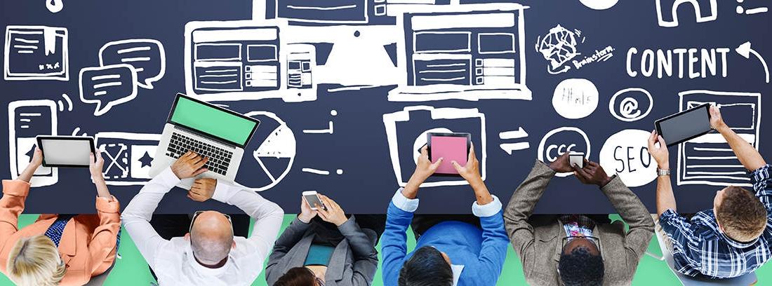 Vista cenital de varias personas con ordenadores y móviles sobre una mesa con gráficos relacionados con diseño y páginas web