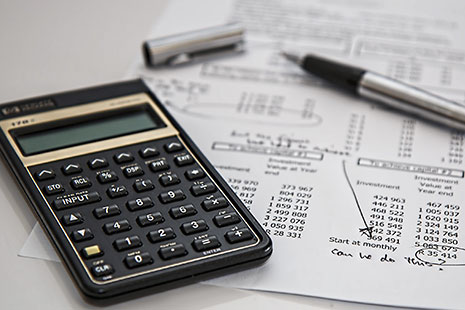 Calculadora sobre papel con números y junto a un bolígrafo