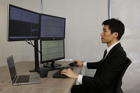 Hombre delante de diferentes monitores y con mano en un teclado de ordenador