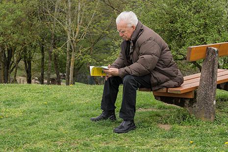 Hombre de pelo blanco leyendo un libro sentado en un banco