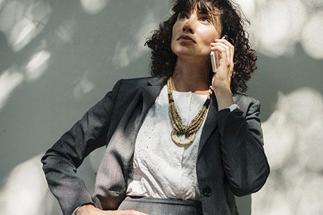 Mujer con mano en la cintura y teléfono móvil junto a la oreja
