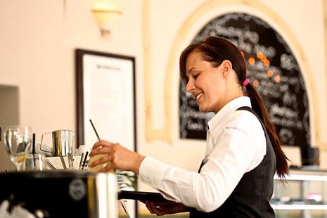 Mujer con camisa blanca y chaleco negro sujeta un vaso y una bandeja