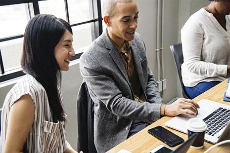 Mujer joven junto a hombre joven con mano sobre teclado de ordenador portátil