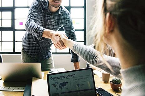 Hombre y mujer estrechan su mano sobre una meda con ordenadores
