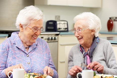 Dos mujeres de pelo blanco delante de taza y plato de comida