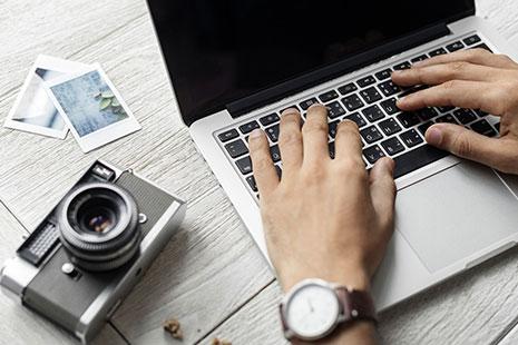 Manos sobre un ordenador portátil, con cámara de foros y dos fotos en papel