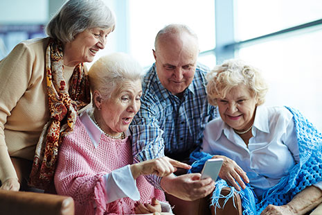 Cuatro personas mayores mirando un teléfono móvil con gesto de agrado