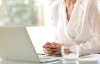 Mujer sonríe delante de un portátil
