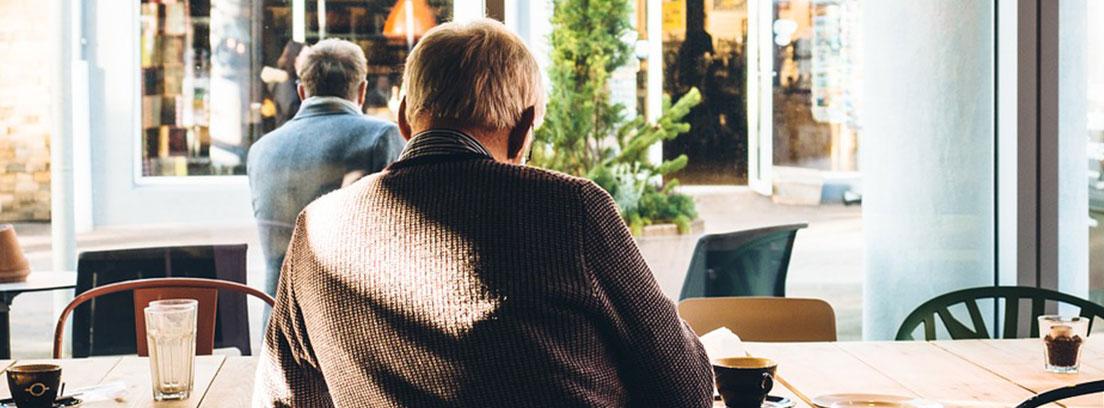 Persona con pelo blanco de espaldas sentado delante de mesa con tazas