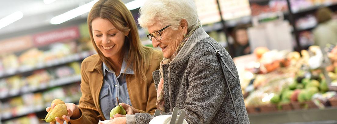 Mujer con pelo blanco junto a otra con bolsas en las que meten frutas