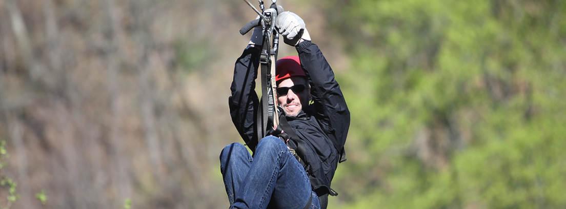 Hombre con casco y gafas de sol suspendido de una cuerda por un arnés