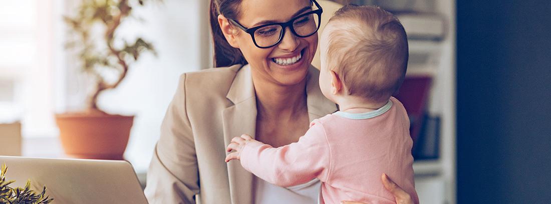 Mujer joven sonriente mirando a un bebé junto a una mesa con un ordenador, una planta y una taza de café