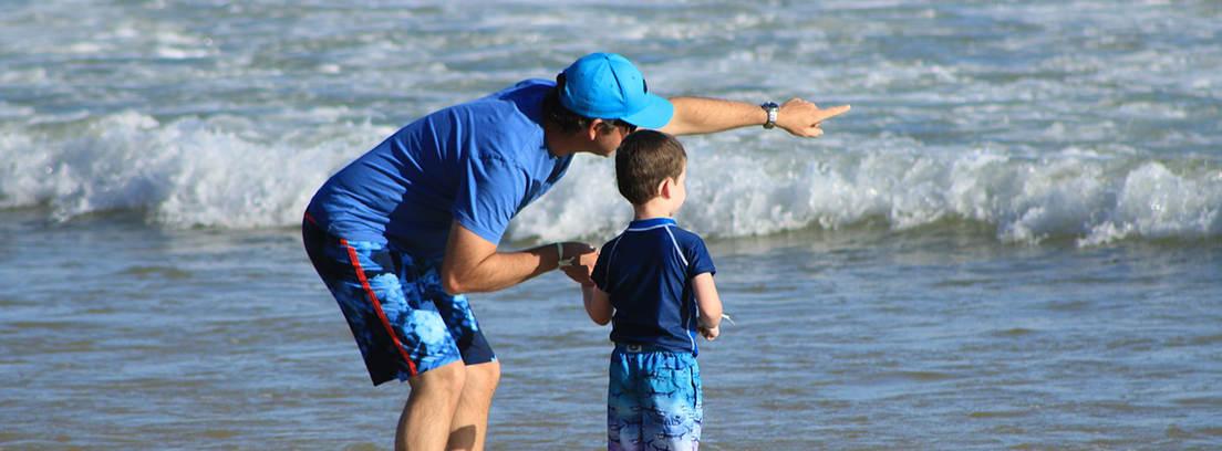 Adulto en la orilla del mar con gorra azul y un niño de la mano