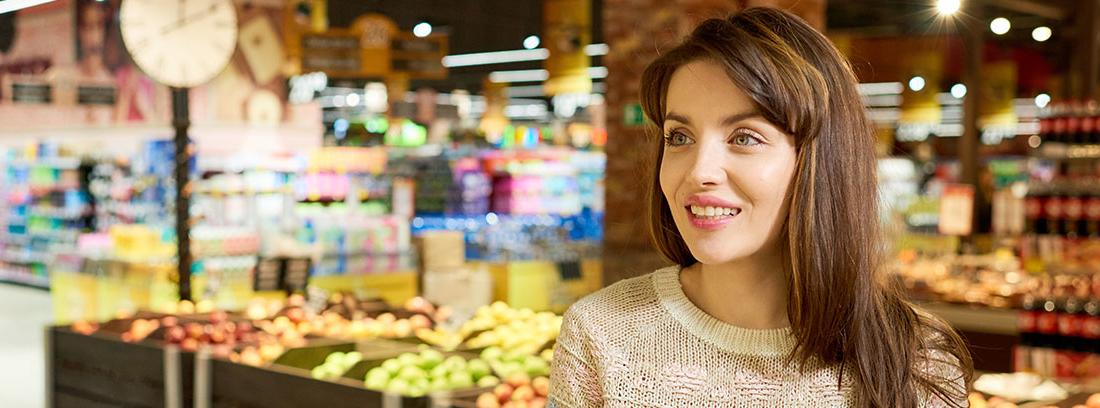 Una mujer sonriente con un mercado al fondo