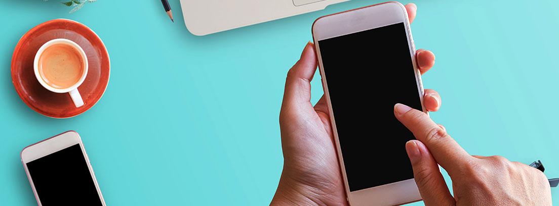 Un teléfono móvil blanco sobre una mesa en la que descansan un teclado de ordenador, dos libretas, un bolígrafo y una calculadora. En la pantalla se muestra la pantalla de inicio de Google Drive. Sobre el teléfono una mano dispuesta a acceder a la aplicación.
