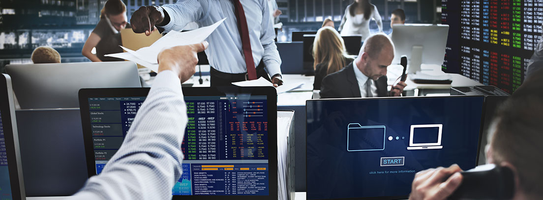 Corredores de bolsa mirando las pantallas de ordenador y hablando por teléfono atentos a las salidas a bolsa de 2018