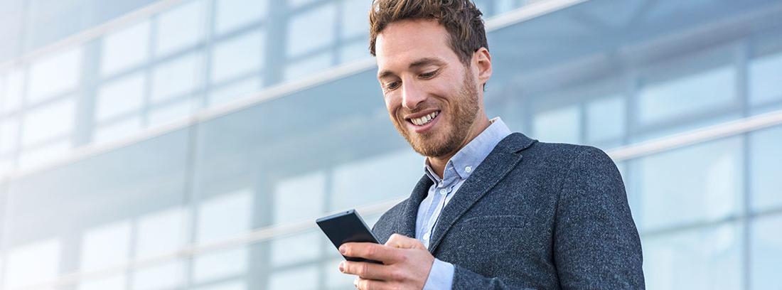 Un joven vestido con un traje gris. Está apoyado en una barandilla metálica. En su mano sostiene un teléfono móvil que mira sonriente. A su espalda un edificio con grandes ventanas de cristal.