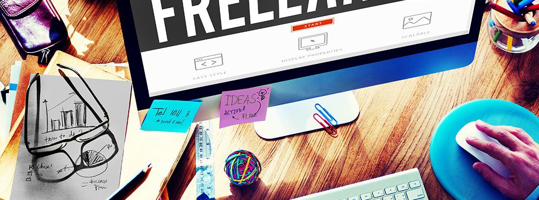 Mesa de despacho en la que se encuentran material de oficina como clips y bolígrafos. Unas manos escriben sobre y teclado blanco y sostienen un ratón. En la pantalla se muestra la palabra FREELANCE en blanco sobre fondo negro.