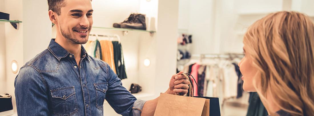 Una mujer joven entrega su tarjeta de crédito a un dependiente joven vestido con una camisa vaquera. El hombre está sonriente y sostiene dos bolsas de papel que entrega a la clienta. AL fondo zapatillas y prendas de ropa expuestas.