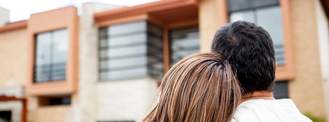 Una pareja joven de espaldas vestida de blanco observa una casa de estilo moderno.