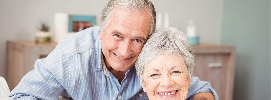 : Una pareja de ancianos posa sonriente. La mujer se encuentra sentada en un sofá gris y va vestida con una camisa blanca. El hombre detrás de ella se apoya en sus hombros con una camisa azul. De fondo una cómoda donde descansan fotos.