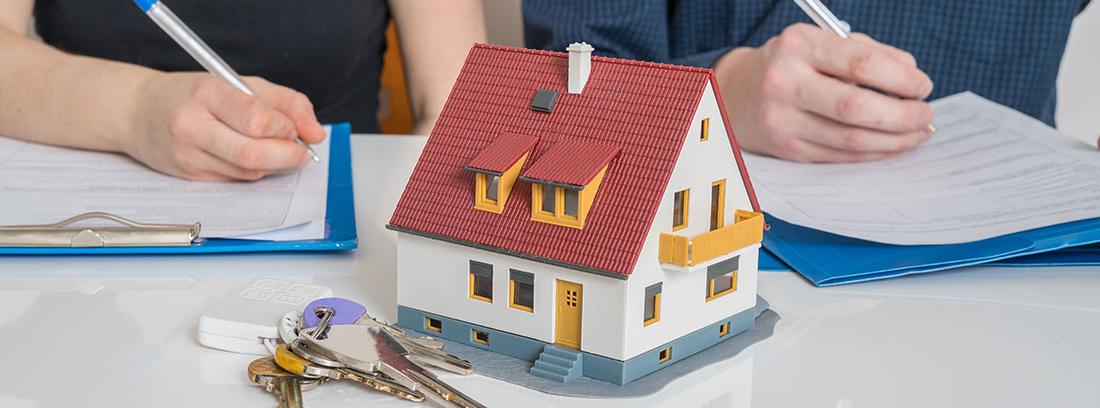 Una pareja firma unos papeles delante de la maqueta de una casa y unas llaves