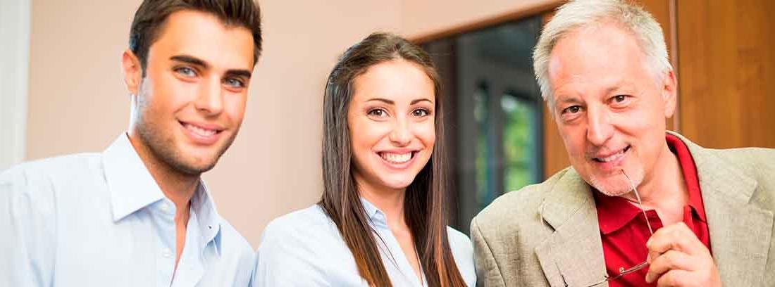 Un chico y una chicha jóvenes y sonrientes vestidos con camisa junto a un hombre con pelo cano vestido de traje marrón con camisa roja. El hombre también está sonriente y sostiene sus gafas apoyadas en la boca