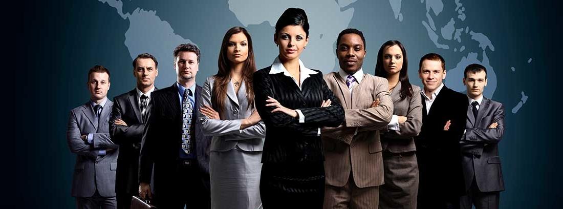 Varios hombres y mujeres de negocios posando con los brazos cruzados. Al frente de grupo colocado en forma triangular destaca una mujer. Al fondo un mapa mundial