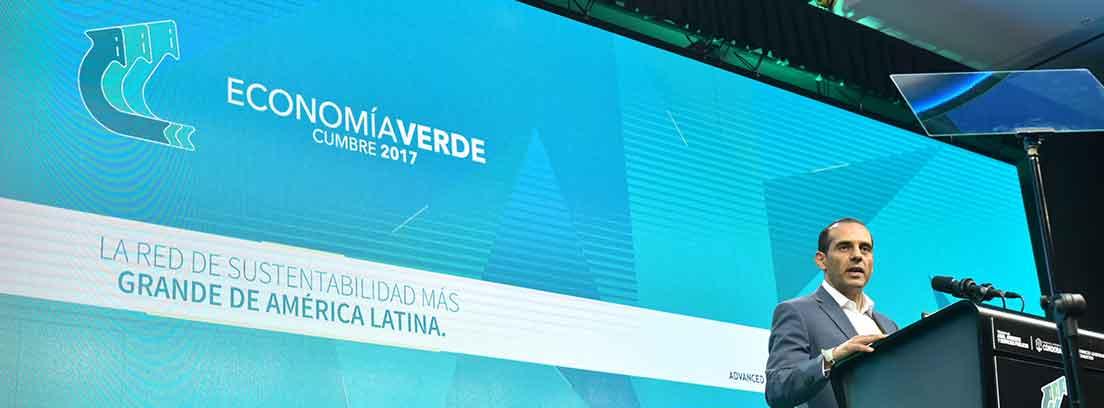 Hombre delante de micrófono en atril y tras el pantalla azul con leyenda economía verde