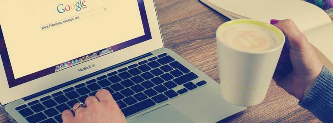 Ordenador portátil abierto con pantalla google y una mano sobre teclado