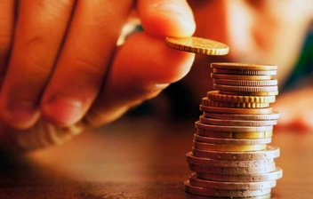 Mano coloca una moneda sobre una columna de ellas